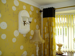 Yellow curtains and matching wallpaper